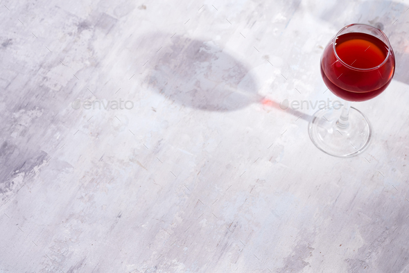 red wine in a wineglass with shadows isolated on stone background - Stock Photo - Images