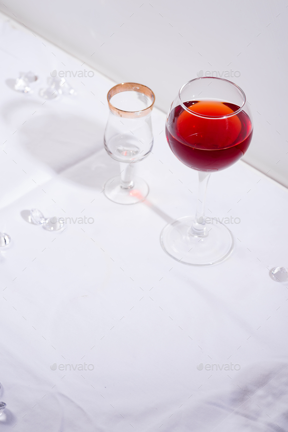 red wine in a wineglass with shadows isolated on white textile background - Stock Photo - Images