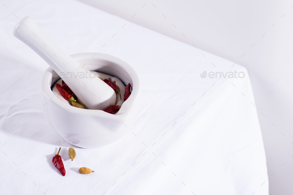 White porcelain mortar and pestle with chili peppers and cardamom isolated on textile table, copy - Stock Photo - Images