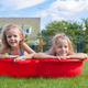 Two little sisters frolicing and splashing in their yard in small pool - PhotoDune Item for Sale