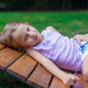 Cute little girl lying on wooden chair outdoor in the park - PhotoDune Item for Sale