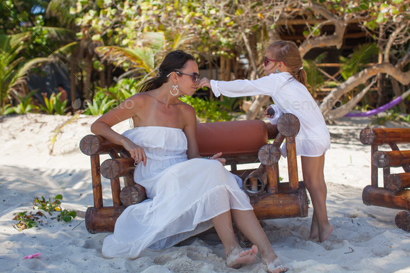 Young mother and her little daughters smelling flowers on tropical beach - Stock Photo - Images