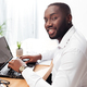 African American businessman happily looking in camera working on his laptop in office - PhotoDune Item for Sale