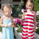 Sweet little girls in a country yard with flowers in their hands - PhotoDune Item for Sale