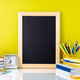 Chalkboard, apple and school supplies on white table by the yellow wall - PhotoDune Item for Sale