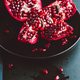 Close up view on a ripe pomegranate in a black plate on a dark background. - PhotoDune Item for Sale