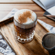 Cup of latte with cinnamon in a glass on a wooden tray. - PhotoDune Item for Sale