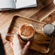 Hand holds a glass of latte served with glass tube on a wooden work desk. - PhotoDune Item for Sale
