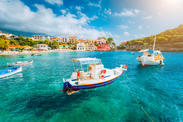 Assos village on Kefalonia island, Greece. White boats in the emerald rippled sea water bay - Stock Photo - Images