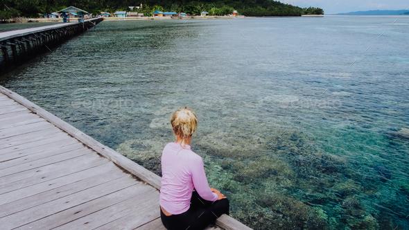 Girl on a wooden jetty near Yenbuba village leading to Mansuar island in Raja Ampat. Beautiful - Stock Photo - Images