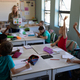 Group of schoolchildren raising their hands in an elementary school classroom - PhotoDune Item for Sale