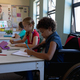 Schoolgirl sitting in a wheelchair in an elementary school classroom - PhotoDune Item for Sale