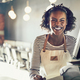 Laughing young African waitress working in a trendy restaurant - PhotoDune Item for Sale