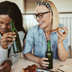 Laughing young businesswomen drinking beers and having pizza after work - PhotoDune Item for Sale