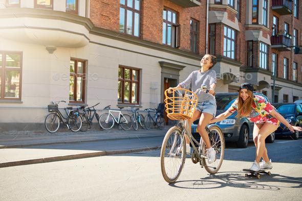 Cute girl on bike pulling friend on skateboard - Stock Photo - Images