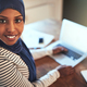 Smiling Arabic female entrepreneur working online with a laptop - PhotoDune Item for Sale