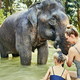 Mother and daughter washing an elephant at an animal sancturay - PhotoDune Item for Sale