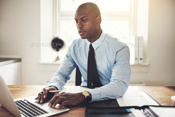Young businessman working on a laptop in an office - Stock Photo - Images