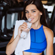 Gorgeous young woman with a towel on her shoulder drinking water from a bottle at the gym - PhotoDune Item for Sale