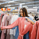 Young woman choosing bathrobe in bed linen store - PhotoDune Item for Sale