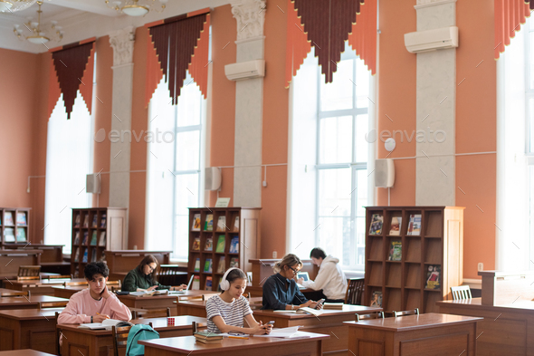 Two rows of desks in college library and students working individually - Stock Photo - Images