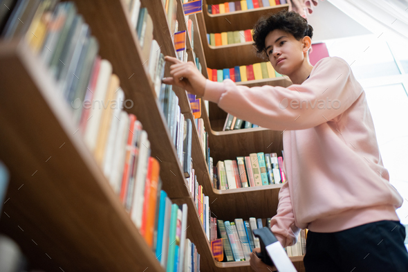 Teenage boy in casualwear taking book from shelf in college library - Stock Photo - Images