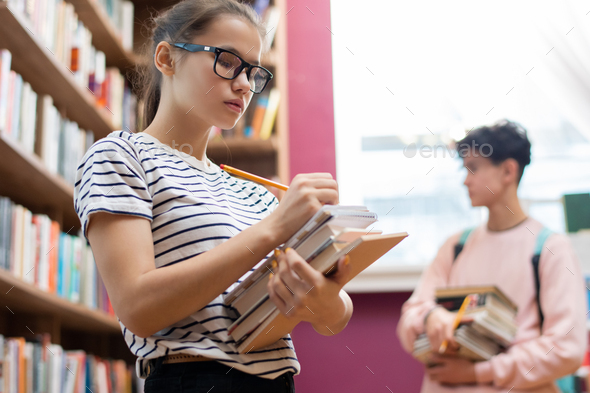 Clever teenager in eyeglasses making notes in notepad on top of stack of books - Stock Photo - Images