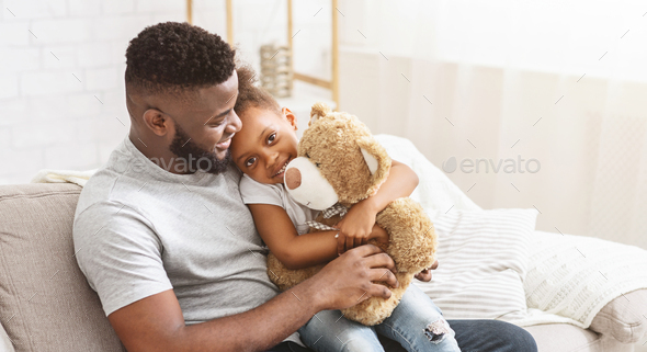 Black father and daughter sitting on sofa at home