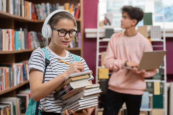 Pretty girl in headphones and eyeglasses making list of literature in library - Stock Photo - Images