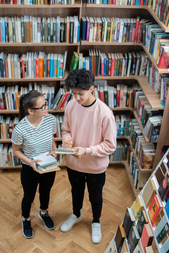 Two casual teenagers standing in college library among shelves with books - Stock Photo - Images