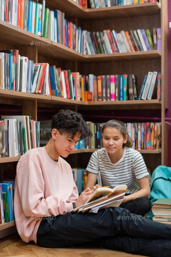 Two clever teenage students discussing passage from story in library - Stock Photo - Images