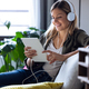 pretty young woman listening to music with headphones and her digital tablet  on sofa at home. - PhotoDune Item for Sale