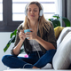 Pretty young woman listening to music with headphones while drinking cup of coffee on sofa at home. - PhotoDune Item for Sale