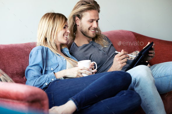 Lovely young couple drawing with they digital tablet while sitting on sofa at home. - Stock Photo - Images