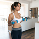 Sporty young woman lifting dumbbells at home. - PhotoDune Item for Sale