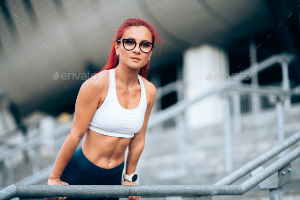 Portrait of attractive red head woman, caucasian woman working out and wearing sportswear - Stock Photo - Images