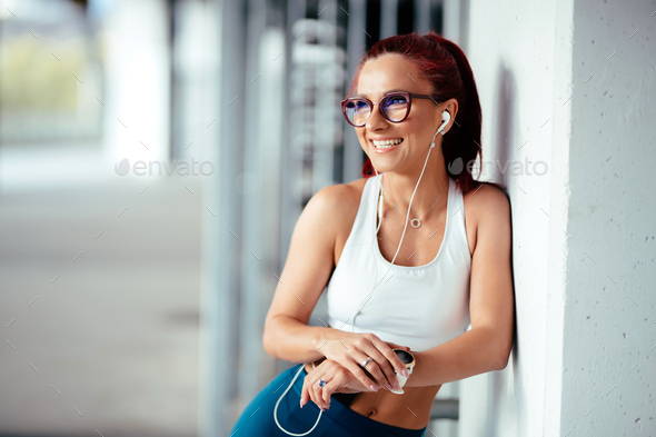 Woman listening to music, doing workout exercises on concrete background - Stock Photo - Images