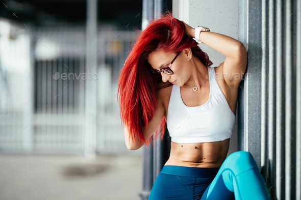 Portrait of fitness girl showing abs during training and working out - Stock Photo - Images