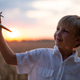 Happy child playing with a toy plane in nature during summer sunset. - PhotoDune Item for Sale
