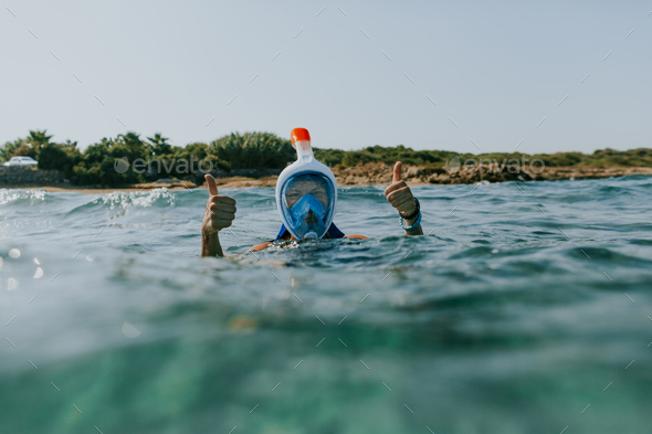 Woman at water surface wearing snorkel mask with thumbs up. - Stock Photo - Images
