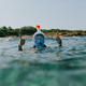 Woman at water surface wearing snorkel mask with thumbs up. - PhotoDune Item for Sale