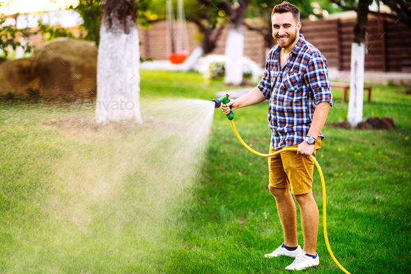 Professional gardener smiling working in garden, using hose and watering lawn and grass - Stock Photo - Images