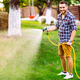 Professional gardener smiling working in garden, using hose and watering lawn and grass - PhotoDune Item for Sale