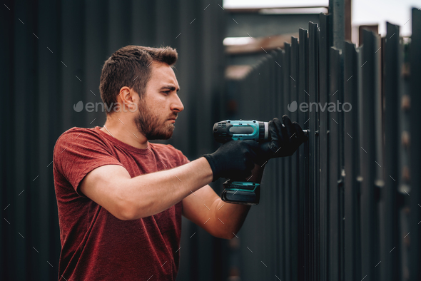 Construction worker using screwdriver for fastening and drilling screws - Stock Photo - Images