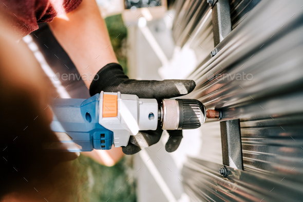 Handyman worker using electrical cord screwdriver for fastening screws into metal fence - Stock Photo - Images