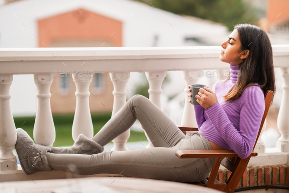 Persian woman on her balcony having a mug of coffee - Stock Photo - Images