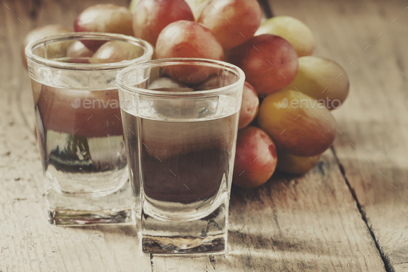 Grappa in small glass and ripe grapes - Stock Photo - Images