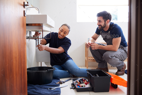 Male Plumber Teaching Female Apprentice To Fix Leaking Sink In Home Bathroom