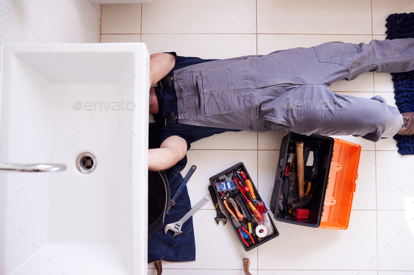 Overhead Shot Of Male Plumber Working To Fix Leaking Sink In Home Bathroom