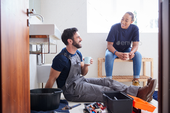 Male Plumber With Female Apprentice Taking A Break From Fixing Leaking Sink In Home Bathroom